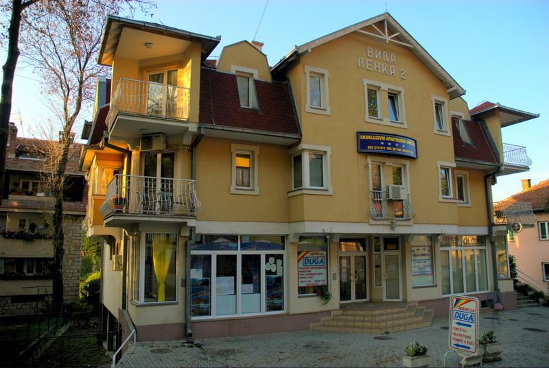 Mikić apartmani - Gde se nalazimo? Apartmani Mikić, nalaze se na samo 100 m od samog centra Vrnjačke Banje, u ulici Beogradska 12a. Iz vile se za svega par minuta stiže do pijace, restorana, picerija, doma zdravlja, centra, pošte, banke, kafića, promenade i parka, i može se reći da Vam je iz apartmana Mikić sve na dohvat ruke.   Ukoliko dolazite sopstvenim prevozom, do Mikić Apartmana možete stići na sledeći način. Pri skretanju sa magistrale ka banji, da bi ste došli do Mikić Apartmana, potrebno je da vozite pravo sve do kružnog toka u samoj banji, odakle takođe nastavljate pravo uporedo sa potokom koji teče pored glavnog banjskog puta. Kada iza sebe ostavite pijacu (sa leve) i Dom zdravlja (sa desne strane), skrenete levo na prvom dozvoljenom skretanju, odakle vas obavezni smer vodi još jednom levo, pravo u Beogradsku ulicu i do Mikić Apartmana. Vila se nalazi sa leve strane, a parking za goste sa sopstvenim vozilom je obezbeđen.  Ukoliko dolazite autobusom, možete uzeti taksi, koji će Vam do vile naplatiti oko 100 dinara, ili krenuti peške. Peške Vam je potrebno između pet i deset minuta od autobuske stanice. U tom slučaju krenete ka pijaci i nastavite pravo ostavljajući pijacu sa Vaše desne strane, nakon čega imate još samo oko 50-ak metara do vile. Između vile i banjske promenade, u najužem centru Vrnjačke Banje,  nalazi se Čajkino brdo.  Do promenade ne morate ići preko ovog brda nego možete i pored pijace, preko centra, za šta će Vam biti potrebno svega oko 5 minuta. Ukoliko rešite da ipak prošetate Omladinskom stazom na Čajkinom brdu, videćete na svom putu crkvu, česmu i letnju pozornicu. Mnogi Čajkino brdo nazivaju ukrasom Vrnjačke Banje, jer ga krase vile i po jedan vek stare, predstavnice mondenskog vrnjačkog stila,  obrasle u cveće i zelenilo. Moćni hrastovi uzdižu se ovim brdom, zajedno sa mnogim drugim rastinjem, a posebno je interesantno u proleće kada ga u bezbroj boja oboji divlje i uzgajano cveće. Južno od vile i suprotno od centra možete krenuti u